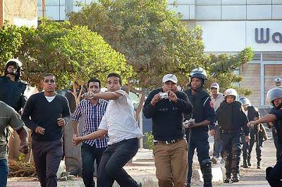 Policias marroquies de paisano y uniforme lanzan piedras contra os manifestantes saharauis