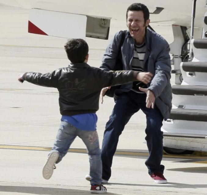 El hijo mayor de Espinosa corre a abrazarlo al pie de la escalerilla del avión en base de Torrejón. A fotografía es de PACO CAMPOS  para EFE. Disculpas por emplearla.