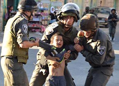 Soldados israelíes forcejean con un niño.