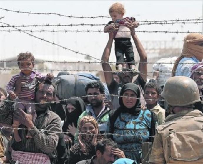 Refugiados sirios aguardan para poder pasar a Turquía.