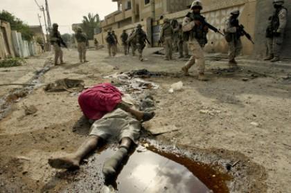 Infantes de marina yanquis pasan por los cadáveres de civiles iraquíes muertos por la ofensiva yanqui contra Faluya, 2004. Foto: AP