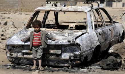 Un niño apoyado en un coche destrozado por bombardeos saudíes. Procedencia: Anadolu Agency/Getty Images